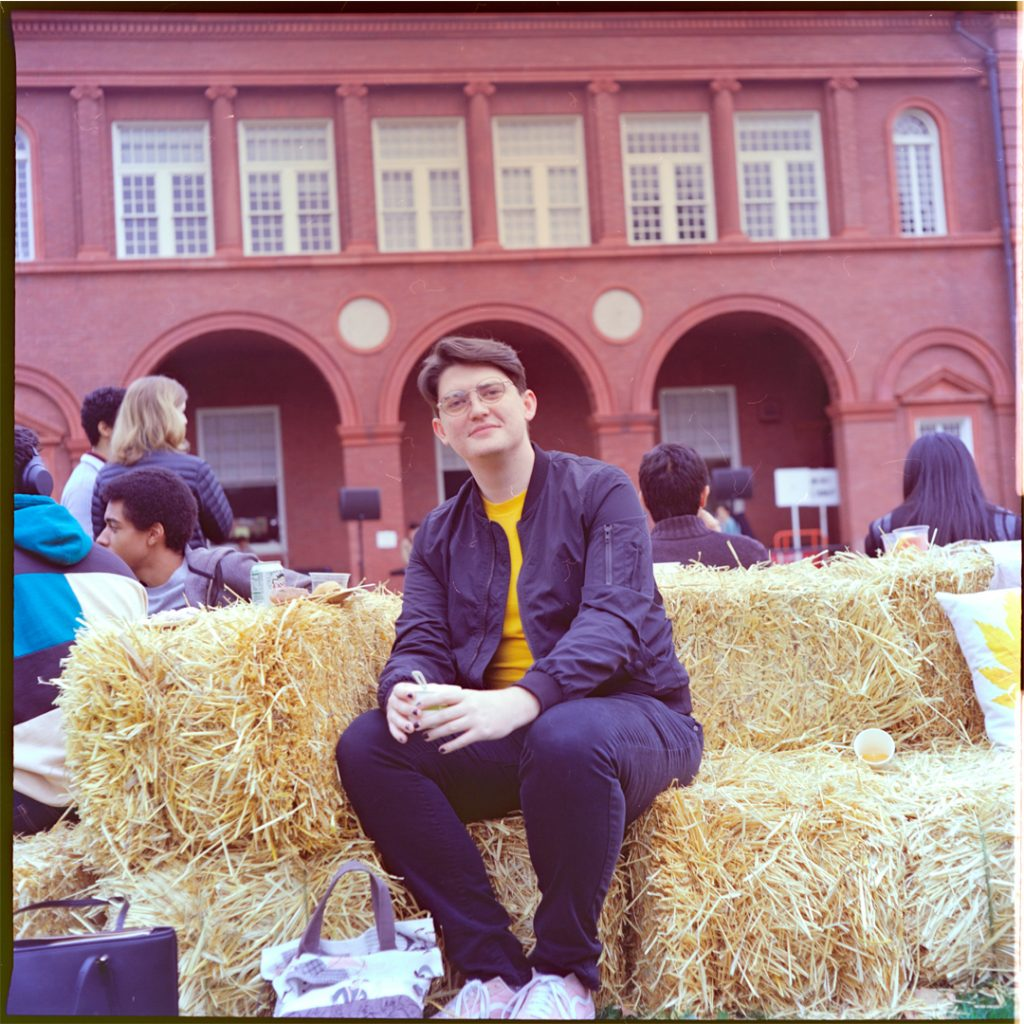 A picture of a young person sitting on a bench made of bales of hay. Behind them is a brick building with 3 archways and a row of windows. Between the person and the building are a group of people talking and listening to a live band. The person is wearing black jeans and a black bomber jacket over a yellow shirt; they wear glasses and have brown hair.