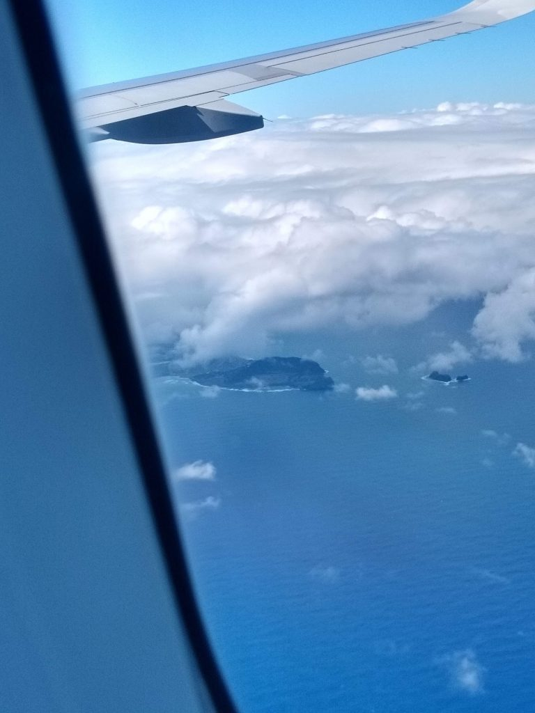 an image of a dark blue ocean and two small islands below light cloud cover, as seen from a plane window